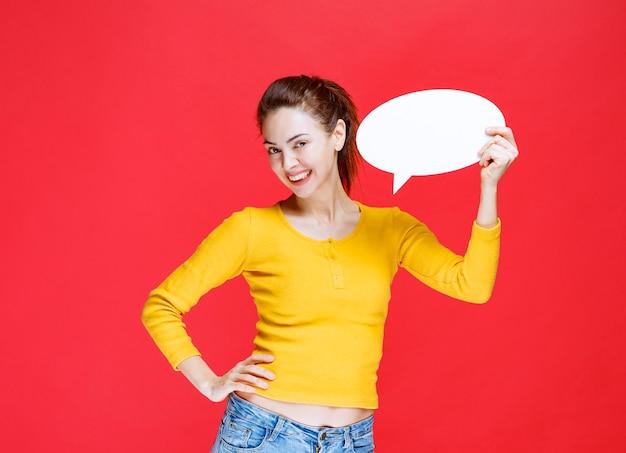 Mulher jovem de camisa amarela segurando um quadro oval de informações