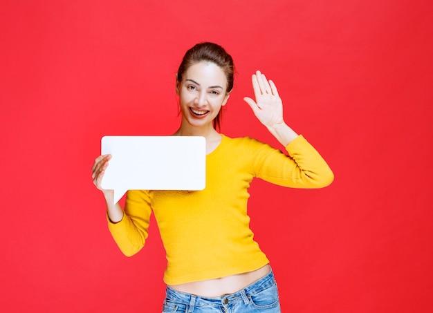 Mulher jovem de camisa amarela segurando um quadro retangular de informações e cumprimentando alguém