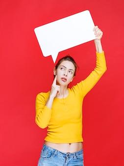 Mulher jovem de camisa amarela segurando um quadro retangular de informações e olhando pensativa