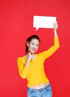 Mulher jovem de camisa amarela segurando um quadro retângulo de informações