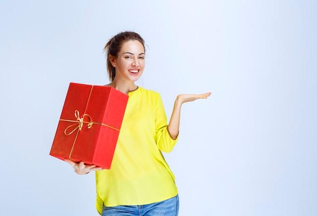 Mulher jovem de camisa amarela segurando uma caixa de presente vermelha e apontando para ela