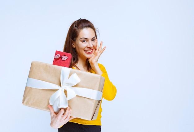 Mulher jovem de camisa amarela segurando uma caixa de presente vermelha e outra de papelão e ficando surpresa e pensativa
