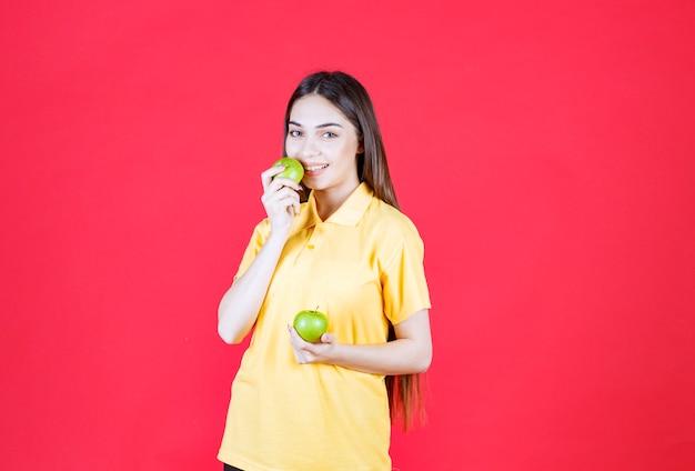 Mulher jovem de camisa amarela segurando uma maçã verde e dando uma mordida