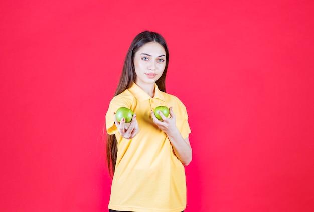 Mulher jovem de camisa amarela segurando uma maçã verde e oferecendo uma ao cliente