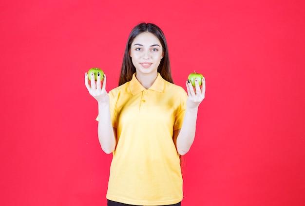 Mulher jovem de camisa amarela segurando uma maçã verde