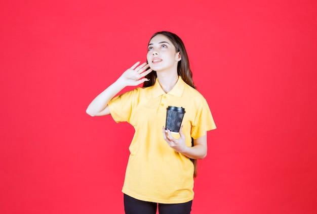 Mulher jovem de camisa amarela segurando uma xícara de café descartável preta e ligando para alguém