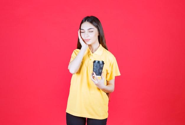 Mulher jovem de camisa amarela segurando uma xícara de café descartável preta e parece cansada e com sono