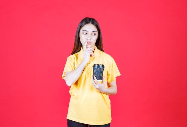 Mulher jovem de camisa amarela segurando uma xícara de café descartável preta, pensando e tendo uma boa ideia