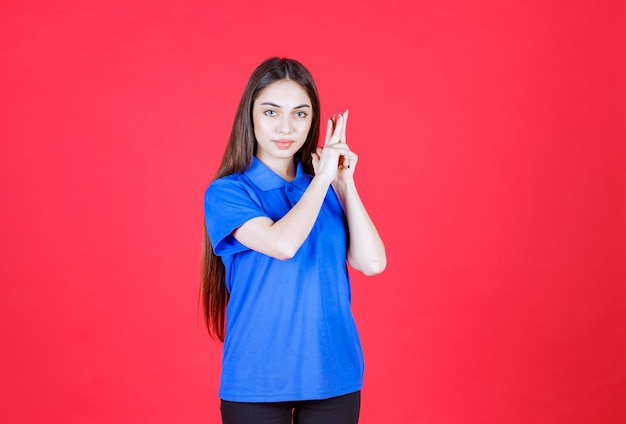 Mulher jovem de camisa azul em pé na parede vermelha e parece confusa e pensativa