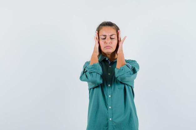 Mulher jovem de camisa azul esfregando a têmpora e parecendo dolorida