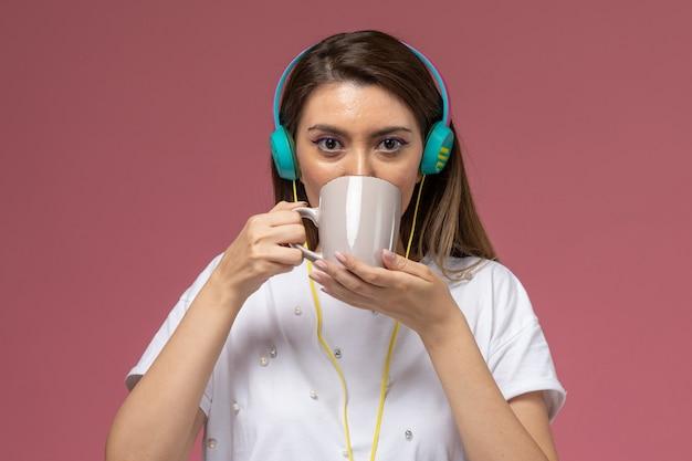 Mulher jovem de camisa branca bebendo café e ouvindo música na parede rosa modelo mulher de frente
