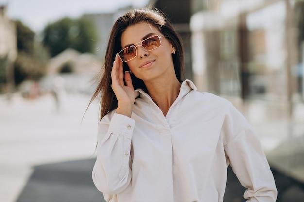 Mulher jovem de camisa branca caminhando pelo lado de fora das ruas de verão