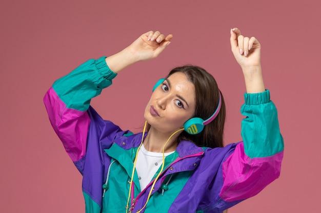 Mulher jovem de camisa branca com casaco colorido de frente, ouvindo música e dançando