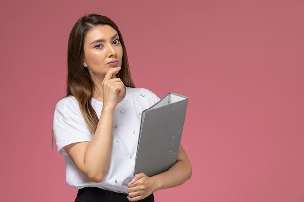 Mulher jovem de camisa branca, de frente, pensando e segurando um arquivo cinza na parede rosa claro, pose de mulher modelo