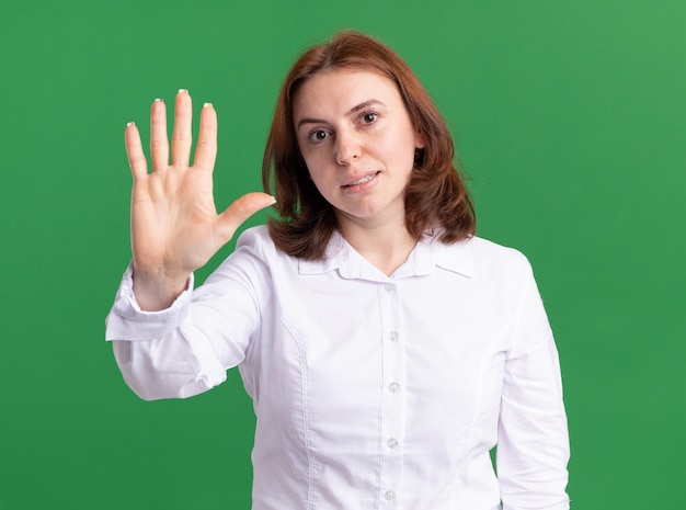Mulher jovem de camisa branca olhando para a frente aparecendo e apontando para cima com os dedos número cinco, sorrindo e olhando para a parede verde