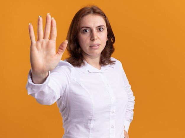Mulher jovem de camisa branca olhando para a frente com uma cara séria, fazendo um gesto de parada com a mão em pé sobre a parede laranja