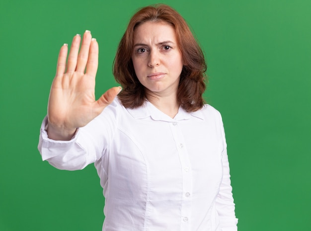 Mulher jovem de camisa branca olhando para a frente com uma cara séria, mostrando um gesto de pare com a mão aberta em pé sobre uma parede verde