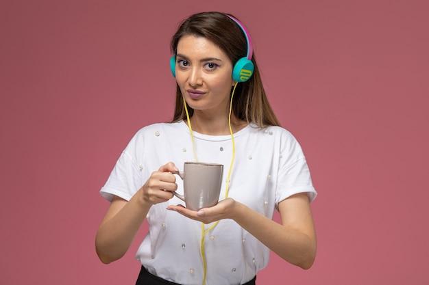 Mulher jovem de camisa branca ouvindo música, de frente, segurando policial com café na parede rosa, cor mulher modelo mulher