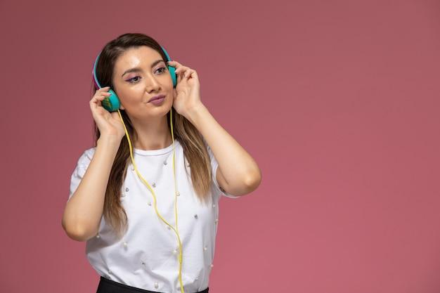 Mulher jovem de camisa branca ouvindo música na parede rosa de frente, modelo de pose de mulher de cor