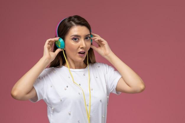 Mulher jovem de camisa branca ouvindo música na parede rosa, modelo mulher de cor de frente