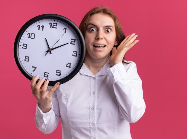 Mulher jovem de camisa branca segurando um relógio de parede olhando para a frente espantada e surpresa em pé sobre a parede rosa