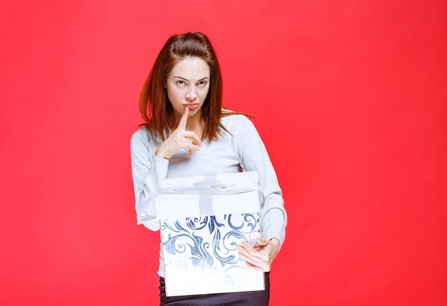 Mulher jovem de camisa branca segurando uma caixa de presente impressa e parece confusa e pensativa