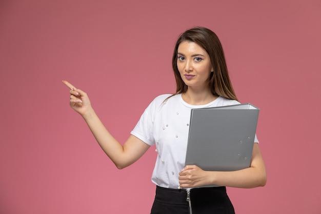 Mulher jovem de camisa branca segurando uma lima cinza na parede rosa