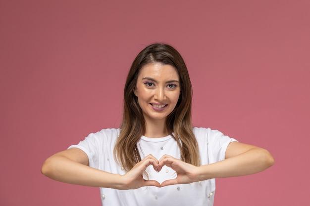 Mulher jovem de camisa branca sorrindo de frente mostrando sinal de coração na parede rosa, modelo de pose de mulher de cor