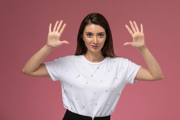 Mulher jovem de camisa branca, vista frontal, posando com as mãos levantadas na parede rosa, modelo mulher de cor