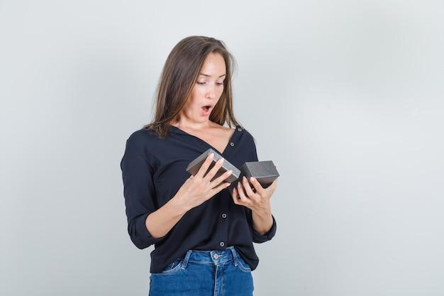 Mulher jovem de camisa preta, shorts jeans, olhando para a caixa do relógio aberta e parecendo surpresa
