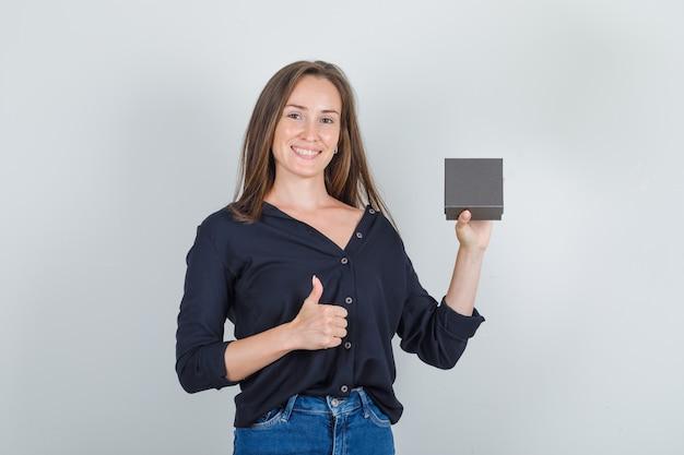 Mulher jovem de camisa preta, shorts jeans, segurando a caixa do relógio com o polegar para cima e parecendo feliz
