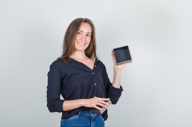 Mulher jovem de camisa preta, shorts jeans, segurando a caixa do relógio vazia e parecendo alegre