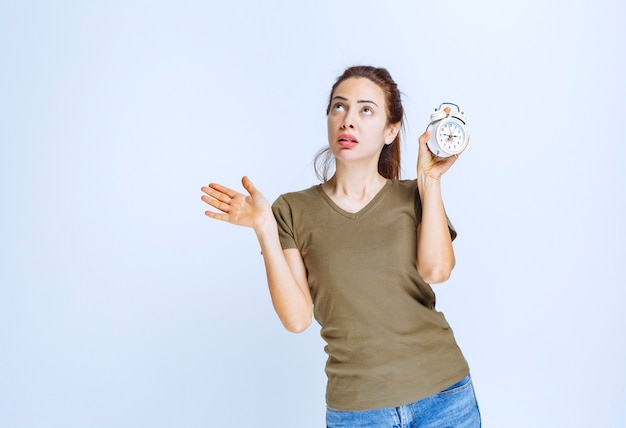 Mulher jovem de camisa verde segurando um despertador e parece confusa