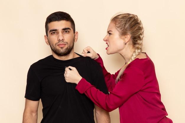 Mulher jovem de camisa vermelha brigando de frente com homem no espaço creme foto emoção violência doméstica