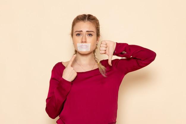 Mulher jovem de camisa vermelha com a boca amarrada de frente mostrando sinal no espaço creme feminino pano feminino violência doméstica