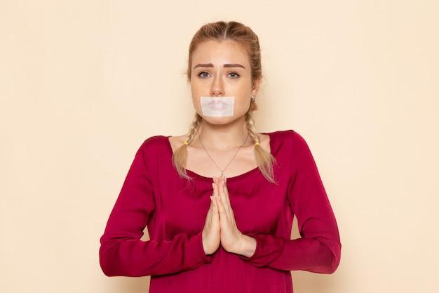 Mulher jovem de camisa vermelha com a boca amarrada de frente rezando na luz do espaço violência doméstica
