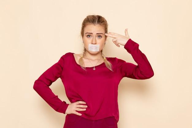 Mulher jovem de camisa vermelha com a boca amarrada no creme espaço emoções foto violência doméstica