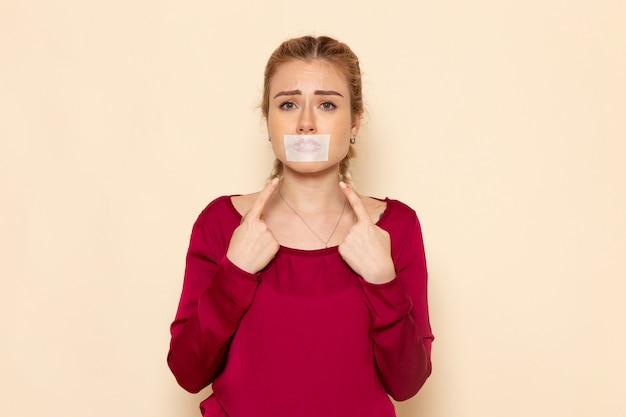 Mulher jovem de camisa vermelha com a boca amarrada no espaço creme emoção foto violência doméstica