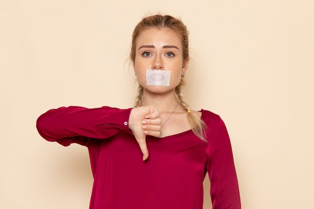Mulher jovem de camisa vermelha com a boca amarrada no espaço creme feminino pano feminino foto violência doméstica