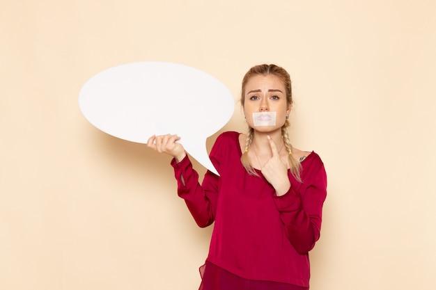 Mulher jovem de camisa vermelha com a boca amarrada segurando uma placa branca no espaço creme feminino pano feminino violência doméstica