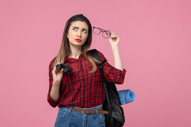 Mulher jovem de camisa vermelha com binóculos no modelo de cor de mulher de fundo rosa