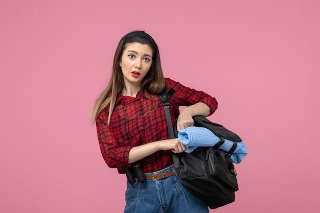 Mulher jovem de camisa vermelha com bolsa no modelo de foto de mulher com fundo rosa
