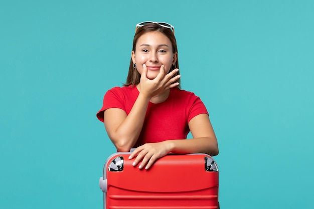 Mulher jovem de camisa vermelha com bolsa vermelha se preparando para as férias no espaço azul.