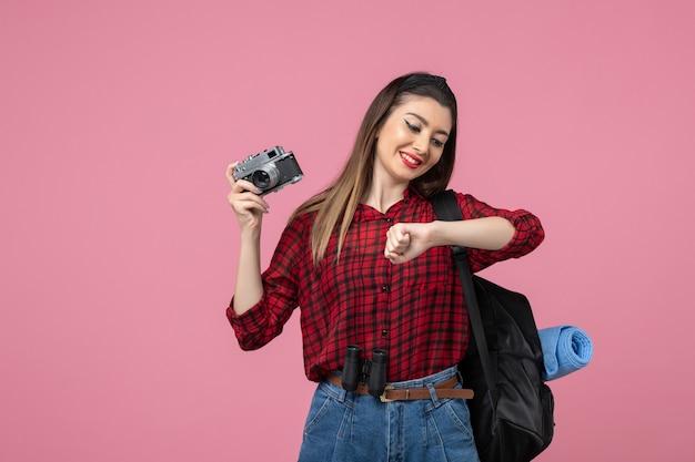 Mulher jovem de camisa vermelha com câmera na foto de modelo de mulher com fundo rosa
