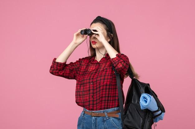 Mulher jovem de camisa vermelha usando binóculos em fundo rosa estudante cor de frente