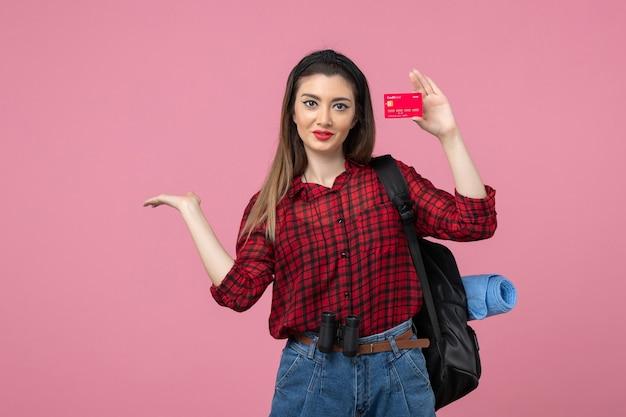 Mulher jovem de camisa vermelha, vista frontal, segurando um cartão do banco na cor rosa mulher humana