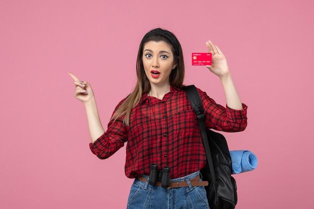 Mulher jovem de camisa vermelha, vista frontal, segurando um cartão do banco na mesa rosa