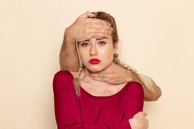 Mulher jovem de camisa vermelha, vista frontal, sofrendo de asfixia com o tecido feminino espaço creme