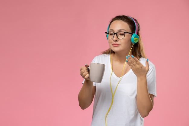 Mulher jovem de camiseta branca, de frente, ouvindo música nos fones de ouvido e segurando uma xícara com chá no fundo rosa