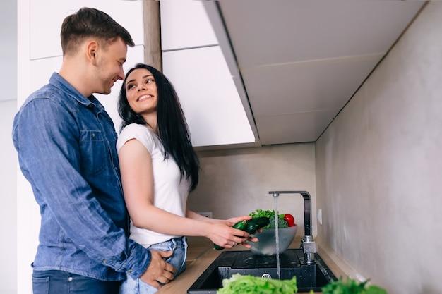 Mulher jovem de camiseta lava vegetais na cozinha o homem abraça gentilmente a garota